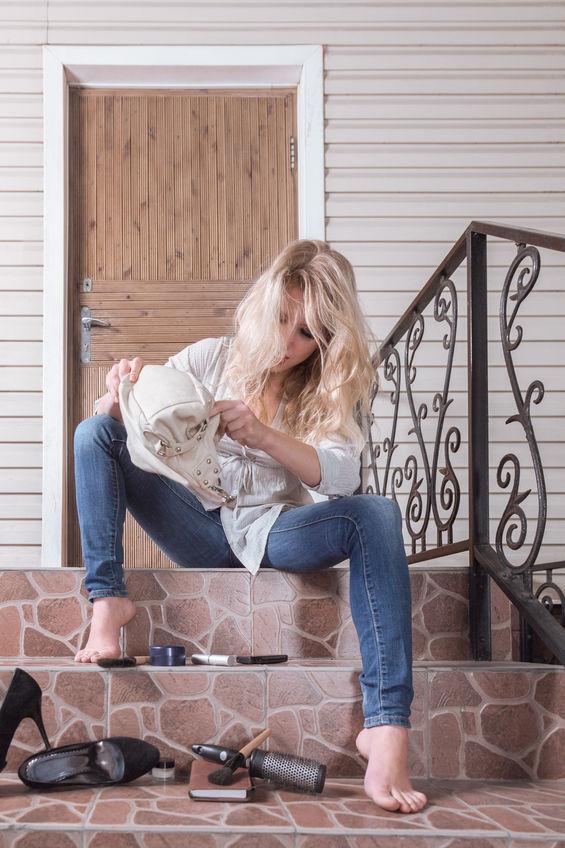 Droevige jonge vrouw die voor de toegangsdeur wacht, omdat ze haar sleutels verloor